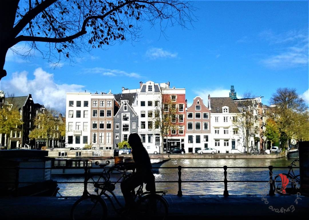 Amsterdam-biciclette-panorama-canali-sole