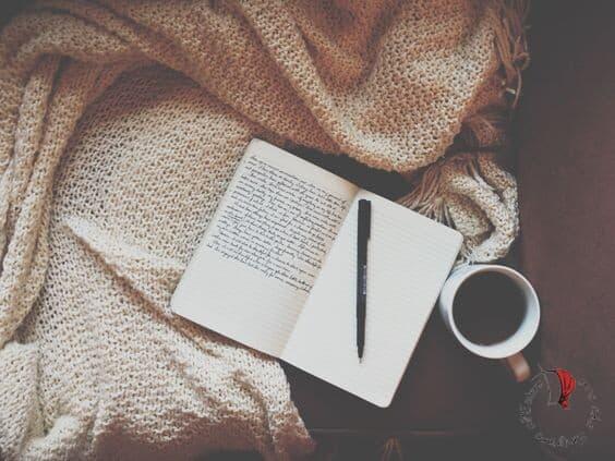 diario con scritte coperta e tazza di caffè